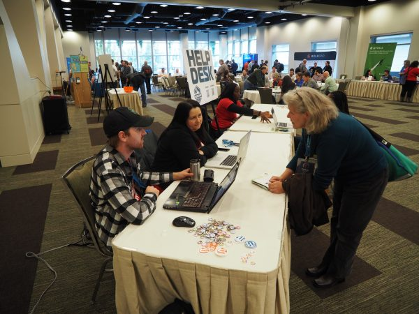 A volunteer and I help a WordCamp attendee at the help desk