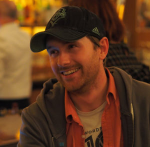 Mark Root-Wiley, wearing Seattle Sounders hat, smiling in conversation