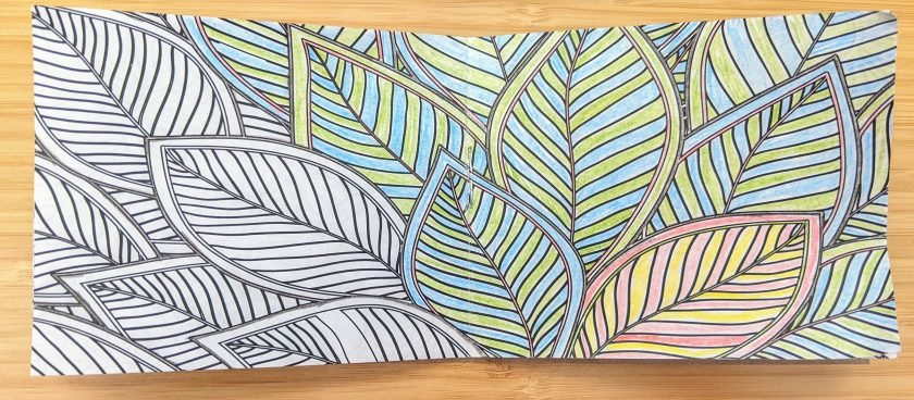 A partially completed tiny coloring book page. A series of overlapping leaves are colored in with blue and green stripes with one yellow and pink leaf differing from the others